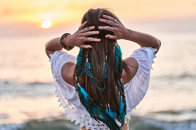 Boho hippie woman with blue feathers in hair