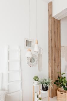 Бохо интерьер гостиной в уютной квартире. минималистичный скандинавский стиль, внутренняя лестница, растения, картины, корзина из ротанга и дизайнерские аксессуары. стильный домашний декорратон.