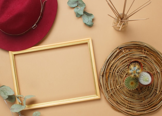 Современный рабочий стол в стиле бохо с рамой, сочными, шляпкой, ароматическими палочками, салфетками.