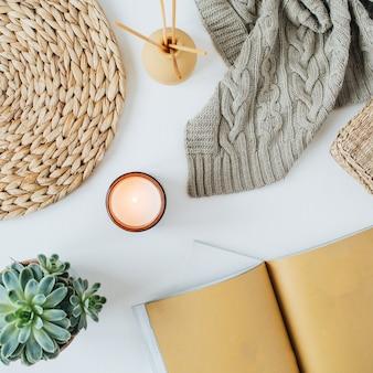 ノートブック、ジューシーなニットチェック柄、キャンドル、アロマスティック、わらの枝編み細工品、白い表面にナプキンを備えた自由奔放に生きるスタイルのモダンなミニマルホームワークスペースデスク