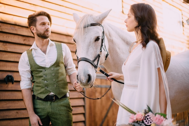 Boho style newlyweds standing near horse, close up