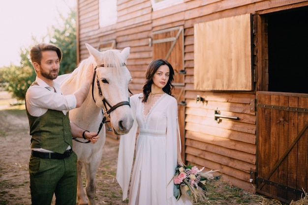 Boho-style newlyweds standing near horse on ranch