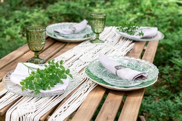 自由奔放に生きるスタイルのウェディングレセプションダイニングテーブル、マクラメのテーブルクロス、素朴な木製のテーブルの装飾