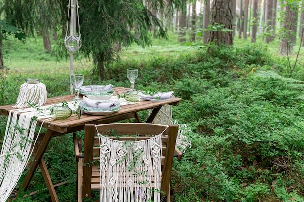 Обеденный стол свадебного приема в стиле бохо со скатертью макраме, украшение на деревенском деревянном столе