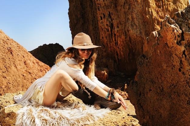 Женский портрет в стиле бохо, сидящий на меху, модной шляпе, солнцезащитных очках и браслетах