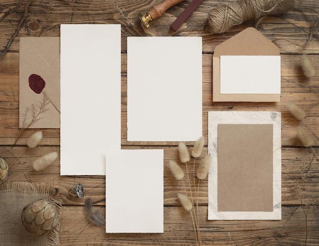 Свадебные пустые открытки и конверты в стиле бохо на деревянном столе с веревкой из засушенных цветов и перьями