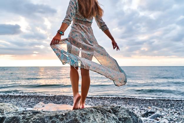 日没で海岸に立っている手を振っている自由奔放に生きる女性