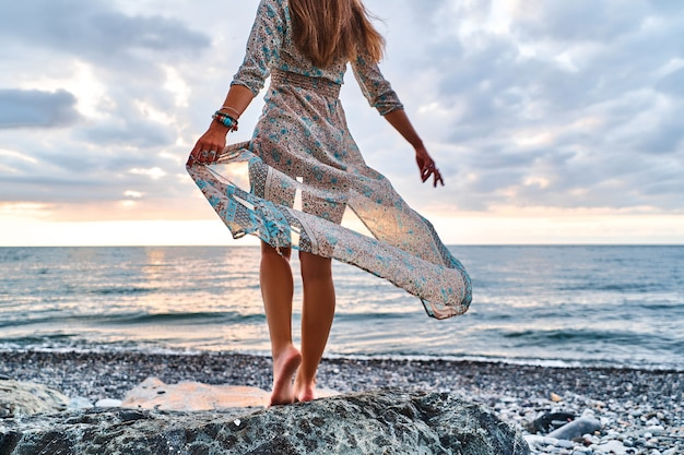 Boho woman with waving dress standing on seashore at sunset