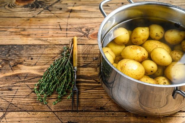 鍋で茹でたベビーポテト。木製の背景。上面図。スペースをコピーします。