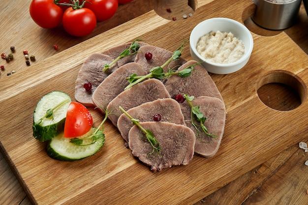 Вареный говяжий язык с соусом и овощами на деревянной доске. аппетитная закуска. лакомство