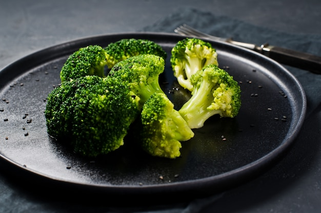 Boiled broccoli on a black plate.
