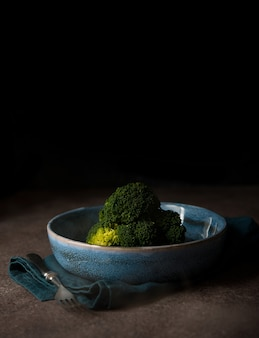 Boiled broccoli in a plate on a black background with a copy of space