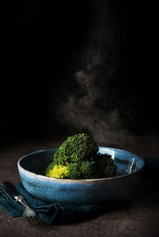 Boiled broccoli with a steam a plate on a black background with a copy of space