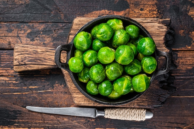 Вареная брюссельская зеленая капуста на сковороде. темный деревянный фон. вид сверху.