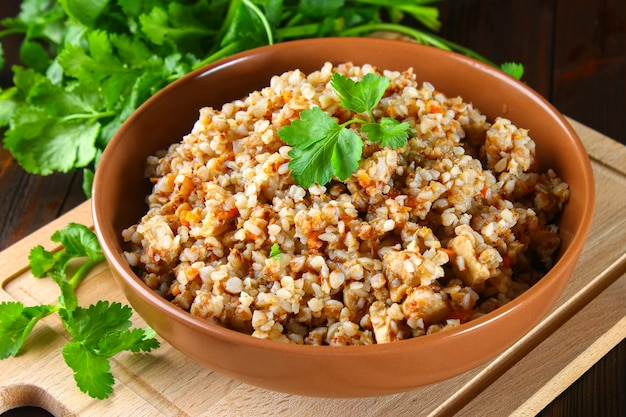 Boiled buckwheat in a bowl with pieces of chicken meat and cilantro on a brown wooden table