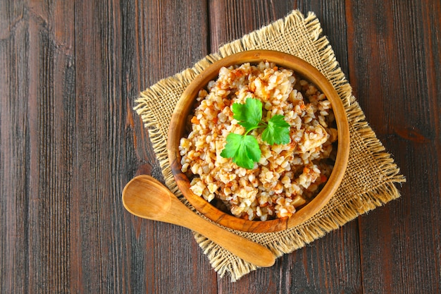 Boiled buckwheat in a bowl with pieces of chicken meat and cilantro on a brown wooden table.