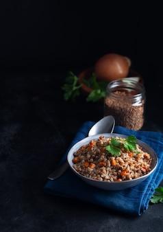 暗い背景にボウルにニンジン、パセリ、バターとソバのシリアルをゆでた。コピースペースと暗い背景に伝統的なロシア料理