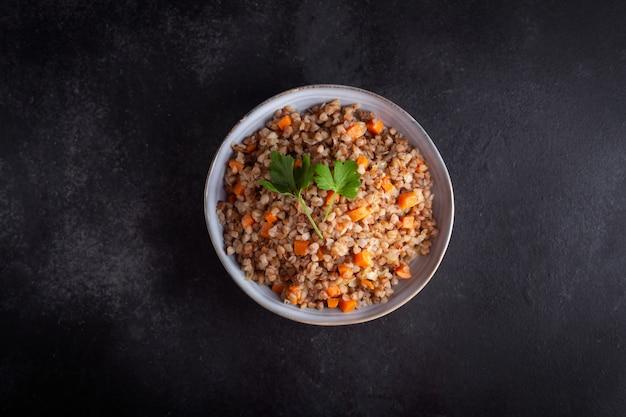 暗い背景にボウルにニンジン、パセリ、バターとソバのシリアルをゆでた。暗い背景に伝統的なロシア料理