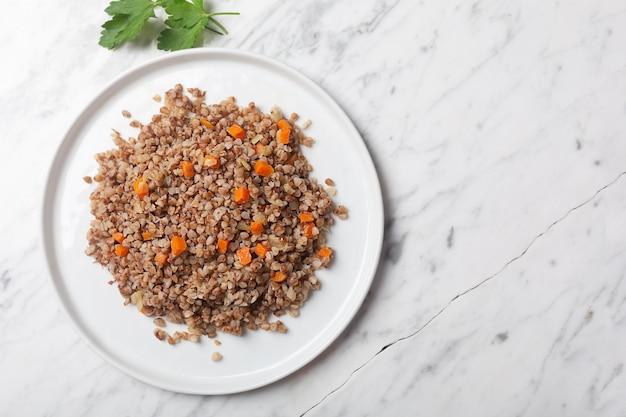 Вареные гречневые хлопья с морковью, петрушкой и маслом в миску на фоне белого камня мрамора. традиционное русское блюдо на сером фоне с копией пространства