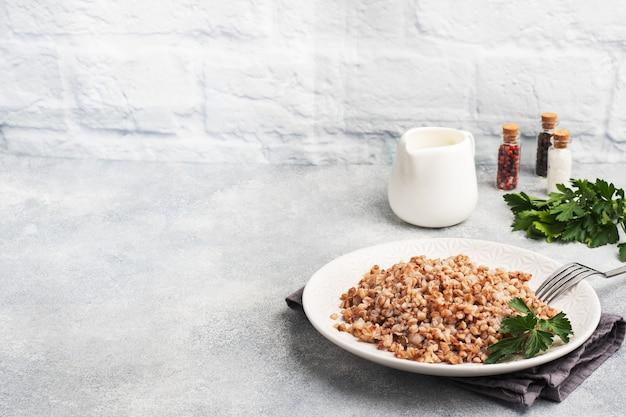 Вареная гречка на тарелке. полезная каша, обогащенная витаминами. копировать пространство,