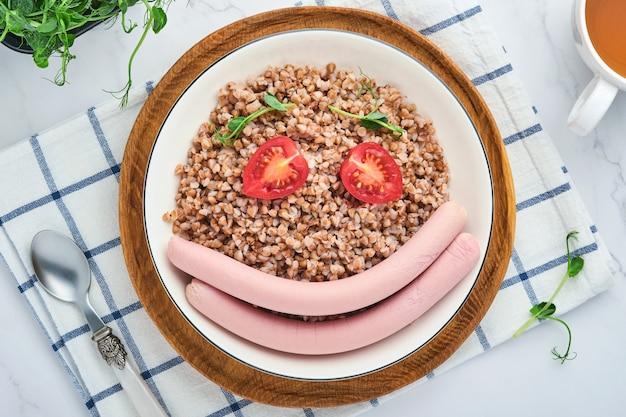 삶은 메밀 죽, 고기 소시지, 토마토, 완두콩의 마이크로그린은 돌 회색 배경의 흰색 접시에 있습니다. 아이들을 위한 재미있는 음식 예술 아이디어 건강한 점심. 평면도.
