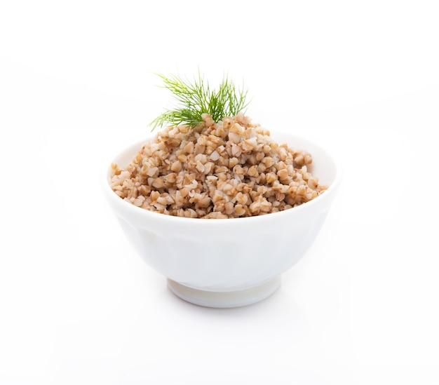 Вареная гречка с укропом в тарелке, изолированные на белом фоне