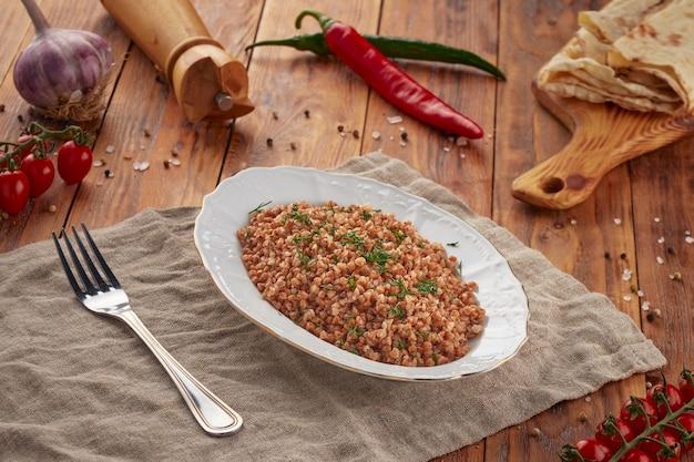 Вареная гречка с зеленью на деревянном фоне, вегетарианская еда