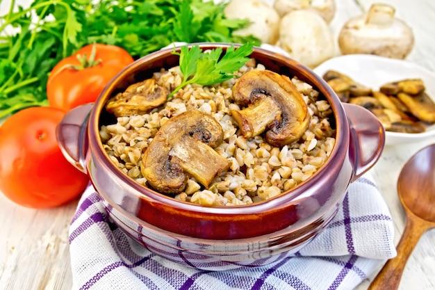 배경 조명 보드에 주방 수건, 파슬리, 토마토, 튀긴 버섯에 갈색 도자기 그릇에 버섯과 삶은 메밀