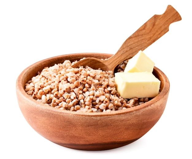 Boiled buckwheat with pieces of butter in a wooden plate close-up on a white background. isolated