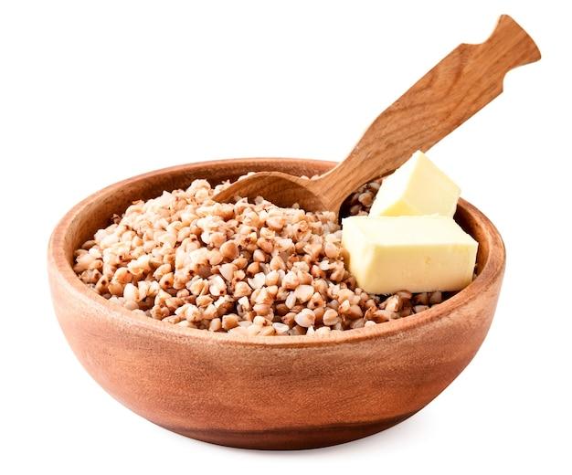 白い背景の上の木の板のクローズアップでバターのかけらと蕎麦をゆでた。孤立