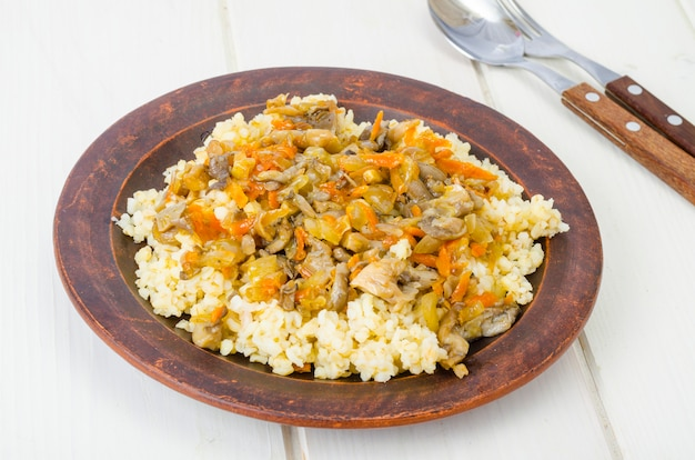 Boiled bulgur groats with stewed vegetables and mushrooms