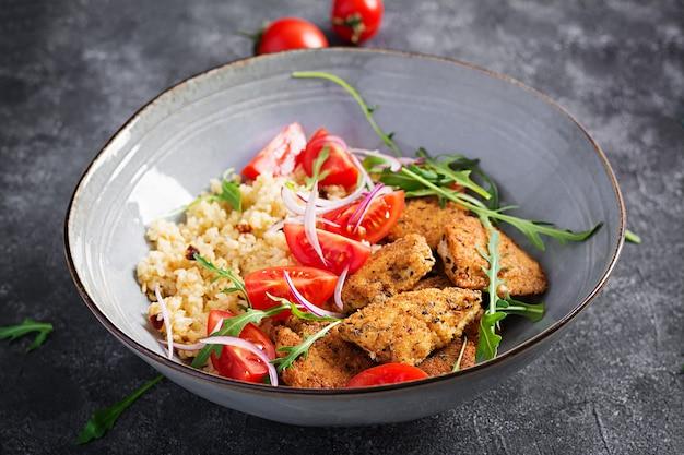 Вареный булгур, жареные куриные наггетсы и салат из свежих помидоров