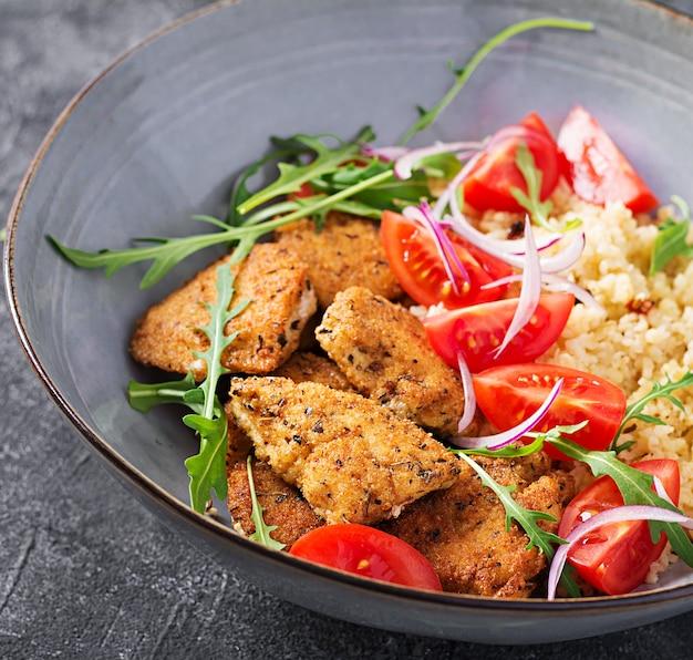 Вареный булгур, жареные куриные наггетсы и салат из свежих помидоров.