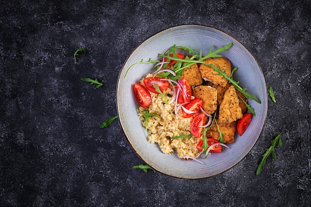 Boiled bulgur, roasted chicken nuggets and fresh tomatoes salad