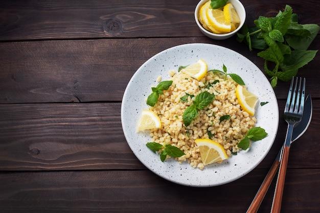プレートに新鮮なレモンとミントを添えたブルグルのボイル。タブーリと呼ばれる伝統的な東洋料理。暗い木製の背景。トップ ビュー、コピー スペース