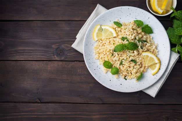 新鮮なレモンとミントを皿に乗せた茹でたブルグル。タブーリと呼ばれる伝統的な東洋料理。暗い木の背景。上面図、コピースペース