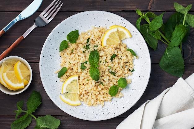 新鮮なレモンとミントを皿に乗せた茹でたブルグル。タブーリと呼ばれる伝統的な東洋料理。暗い木の背景。上面図