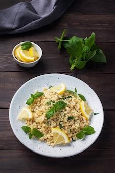 新鮮なレモンとミントを皿に乗せた茹でたブルグル。タブーリと呼ばれる伝統的な東洋料理。暗い木の背景。