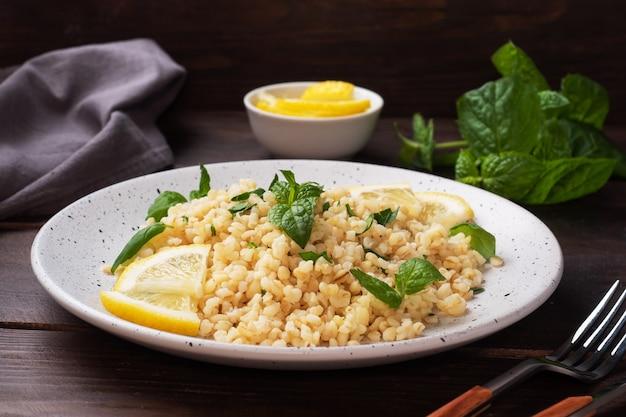 プレートに新鮮なレモンとミントを添えたブルグルのボイル。タブーリと呼ばれる伝統的な東洋料理。暗い木の表面。