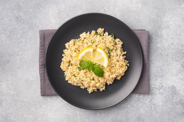 新鮮なレモンとミントを皿に乗せた茹でたブルグル。タブーリと呼ばれる伝統的な東洋料理。灰色のコンクリートの背景上面図、コピースペース
