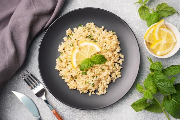 新鮮なレモンとミントを皿に乗せた茹でたブルグル。タブーリと呼ばれる伝統的な東洋料理。灰色のコンクリートの背景