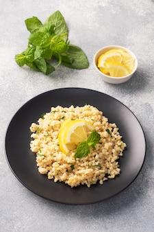 プレートに新鮮なレモンとミントを添えたブルグルのボイル。タブーリと呼ばれる伝統的な東洋料理。灰色のコンクリート面