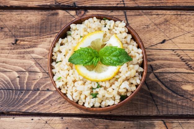 新鮮なレモンとミントを皿に乗せた茹でたブルグル。タブーリと呼ばれる伝統的な東洋料理。木製の背景素朴な上面図、コピースペース