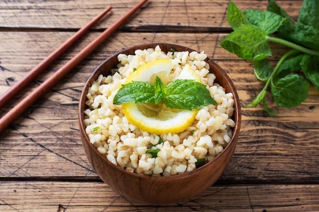 新鮮なレモンとミントを皿に乗せた茹でたブルグル。タブーリと呼ばれる伝統的な東洋料理。素朴な木製の背景