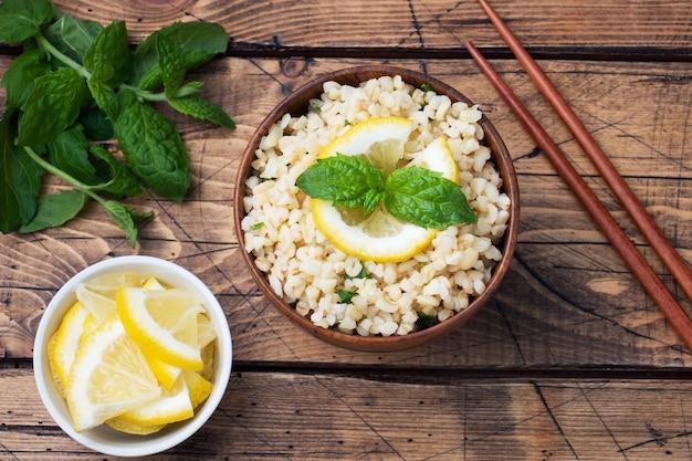 プレートに新鮮なレモンとミントを添えたブルグルのボイル。タブーリと呼ばれる伝統的な東洋料理。木の表面の素朴なトップ ビュー、コピー スペース