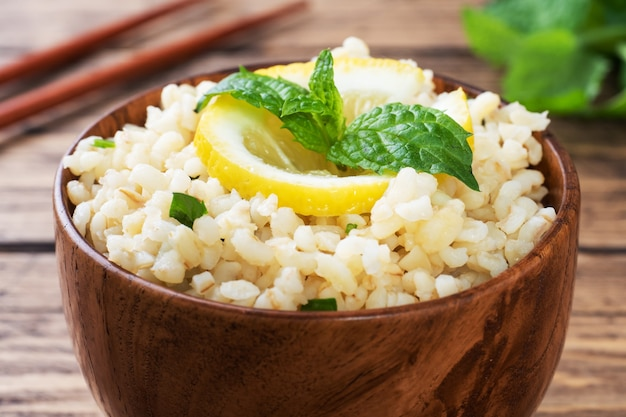 プレートに新鮮なレモンとミントを添えたブルグルのボイル。タブーリと呼ばれる伝統的な東洋料理。素朴な木の表面