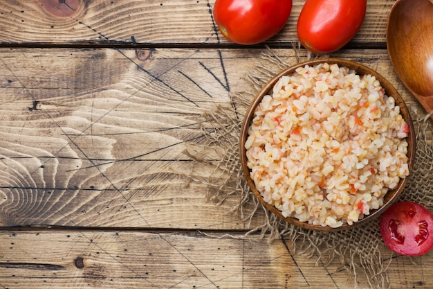 Boiled bulgur with tomatoes in a wooden bowl.