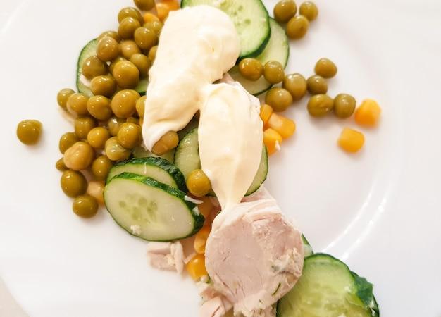 鶏の胸肉をグリーンボイルドエンドウ豆、キュウリ、ソースを添えて白い皿に茹でたもの。健康的なバランスの取れた栄養、ダイエットの概念