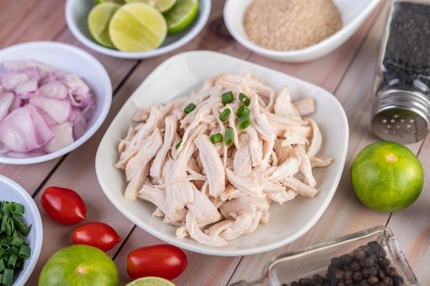Pollo bollito tagliato a pezzi in un piatto bianco su un tavolo di legno.