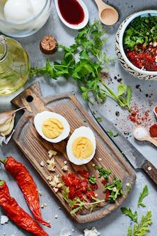 ゆで鶏卵。ゆでた卵のマリネを野菜、ハーブ、スパイス、トマトソースで調理するプロセス。
